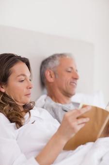 Портрет женщины, читающей книгу, пока ее муж читает