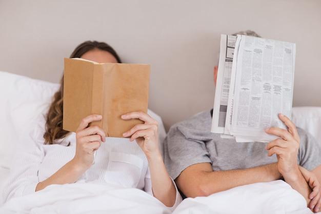 Женщина читает книгу, пока ее спутник читает газету