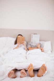 Портрет женщины, читающей книгу, пока ее спутник читает