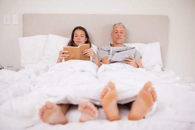 Человек читает новости, пока его жена читает книгу