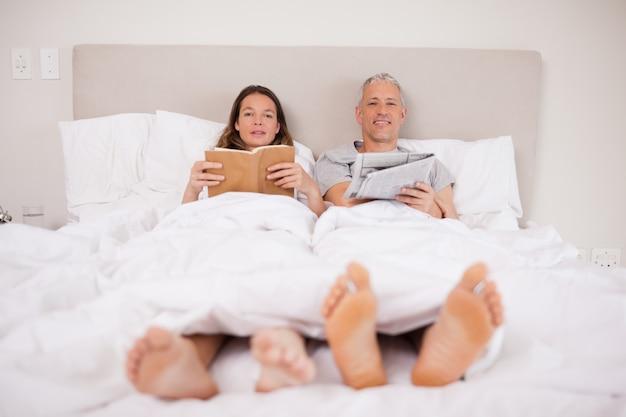 Мужчина читает газету, пока его жена читает книгу