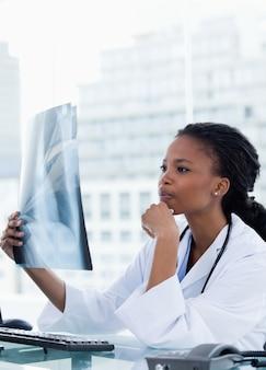 Портрет женщины-врача, глядя на набор рентгеновских лучей