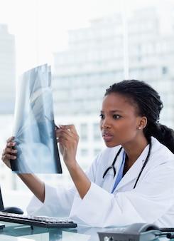 Портрет сфокусированной женщины-врача, глядя на набор рентгеновских лучей