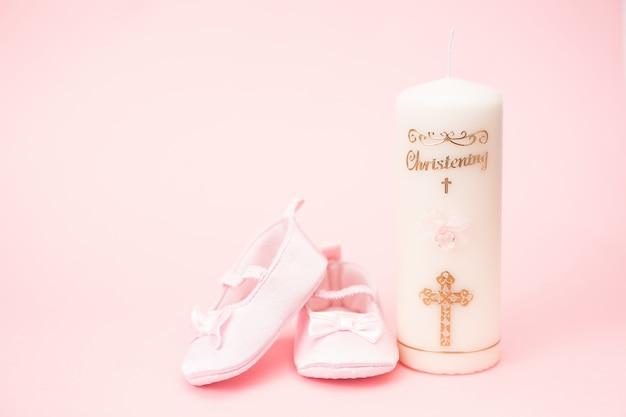 ピンクの赤ちゃんのブーツとコピースペースでキャンドルを唱える