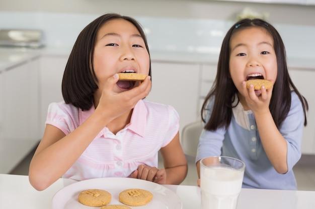 キッチンでクッキーとミルクを楽しむ女の子