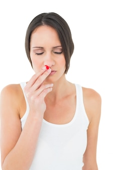 出血鼻を持つカジュアルな若い女性