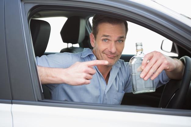 ウォッカの空のボトルを見せている男