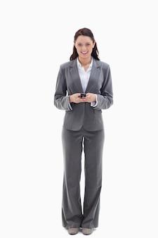 彼女の携帯電話を持っている間、笑顔のビジネスマン