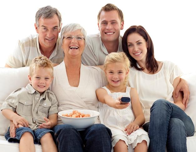 Семья смотрит телевизор и ест чипсы дома