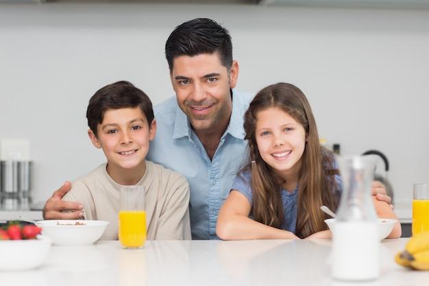 父親、キッチンで朝食を楽しむ子供たち