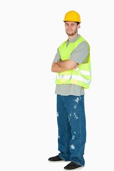 Вид сбоку улыбается молодой строитель со сложенными руками