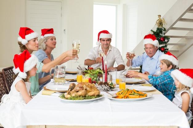 クリスマスの食事をしながら家族はワインをトースト