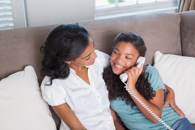 幸せなお母さんと娘は一緒にソファに電話で