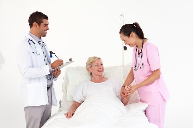 フレンドリーな看護師と医師の間に横たわる笑顔患者
