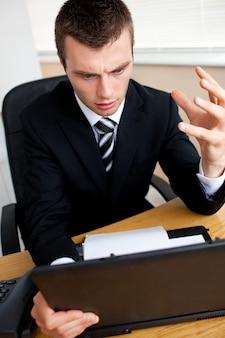 Удивленный бизнесмен, глядя на свой ноутбук