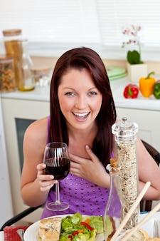 家庭でワインのガラスを保持して彼女の食事を食べる明るい女性