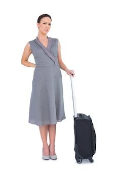 痛い背中に苦しんでいるスーツケースを持つゴージャスな女性