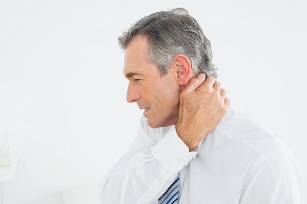 頚部の痛みを患っている成熟した男