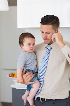 携帯電話を使っている間、赤ちゃんを運んでいるビジネスマン