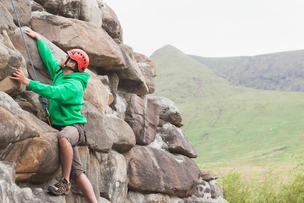 大規模な岩の顔をスケーリング焦点を当てた男
