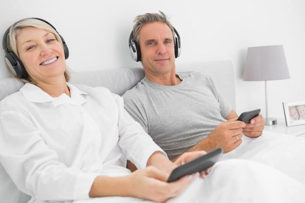 スマートフォンでカップルを音楽に笑う