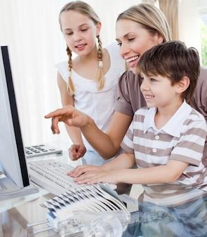 幸せな母と彼女の子供たちは、コンピュータを使って