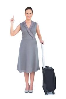 彼女のスーツケースで彼女の指を指す明るい豪華な女性