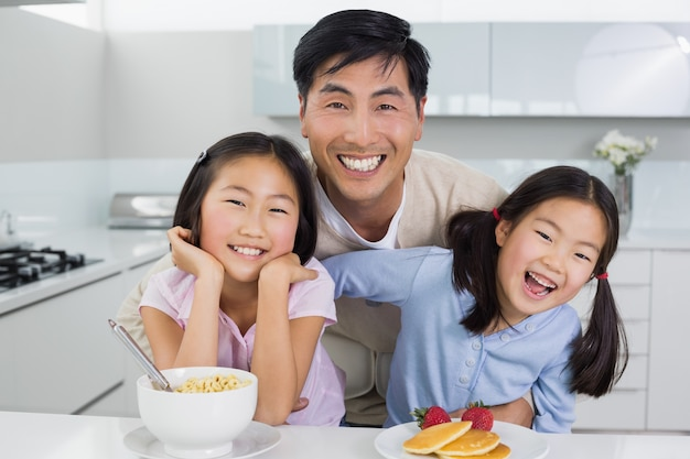 幸せな娘と一緒に笑顔の男がキッチンで朝食を取る