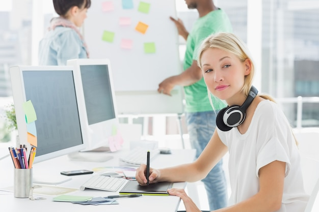 Художник рисует что-то на графическом планшете с коллегами позади в офисе