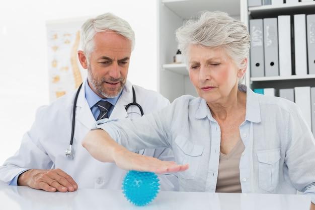 ストレスバスターボールを使用しているシニア患者の男性医者
