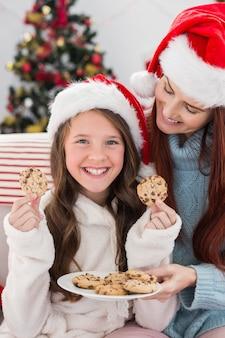 お母さんと娘がソファに座ってクッキーで