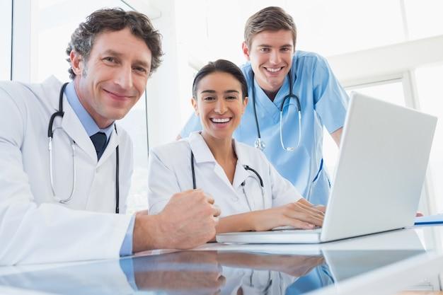 カメラに笑顔の医師のチーム