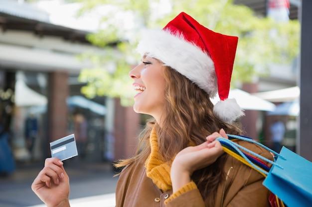 サンタの帽子とショッピングバッグを持つ笑顔の女性