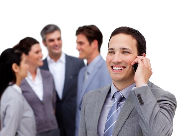 彼のチームから離れて立って電話でハンサムなビジネスマン