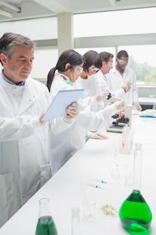 Химик проводит исследования с планшетным пк