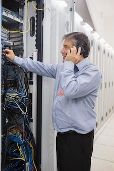 電話をかけながら電線を固定する男