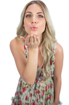 Соблазнительная блондинка в цветущем платье, отправляющая поцелуй