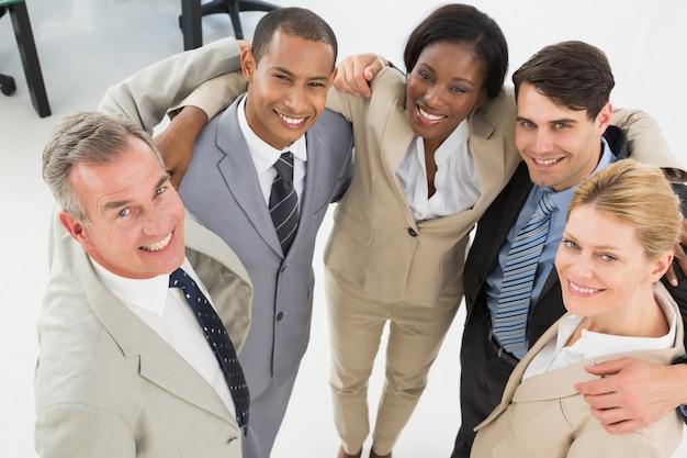 ビジネスのチームを包み込み、カメラで笑って閉じる