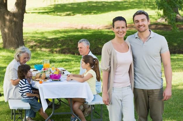 芝生で昼食を取る家族とカップル