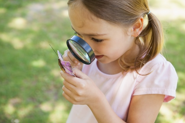 公園で虫眼鏡と蝶を調べる少女