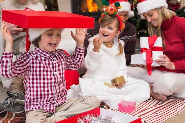 家族と一緒に床に座っている贈り物で遊んでいる息子