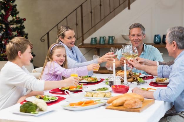 クリスマスディナーで白ワインを焼く家族