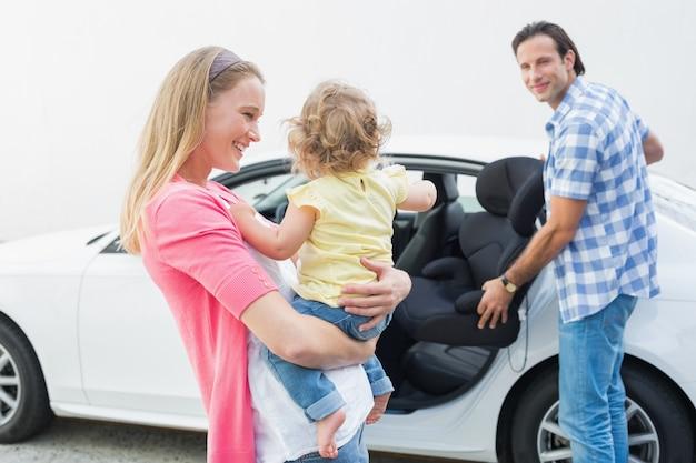 Родители, несущие ребенка и автокресло