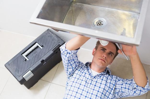 バスルームの洗面器の排水を修理する配管工
