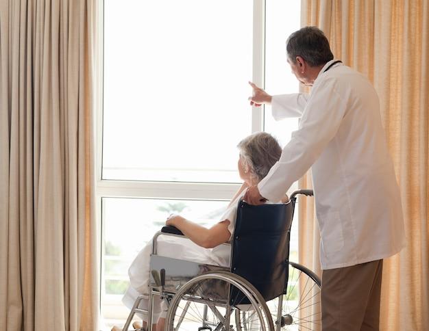 彼の患者が窓を見ている医者