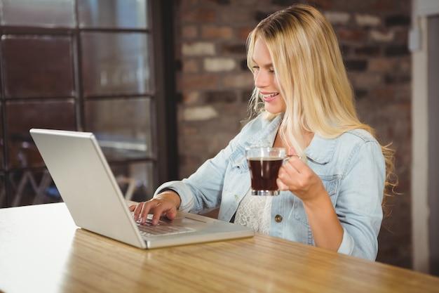コーヒーを飲み、ラップトップで入力する笑顔の女性