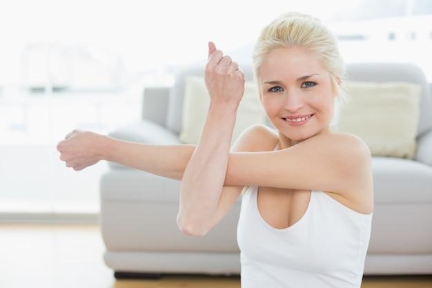 フィットネスのスタジオで手を伸ばして笑顔のスポーティな女性