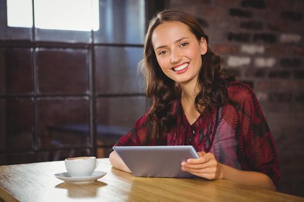 コーヒーを持ち、タブレットを持っている笑顔のブルネット