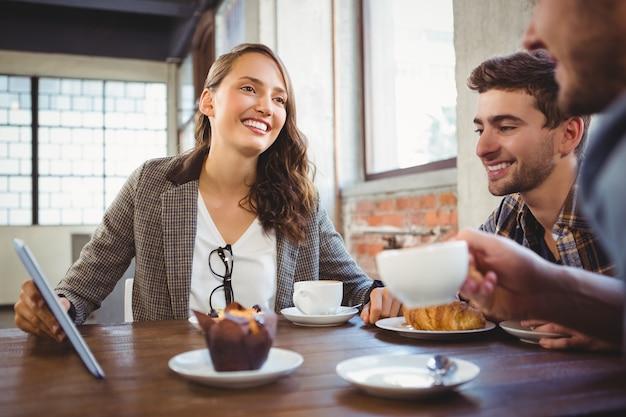 コーヒーを楽しんでタブレットで使う笑顔の友達