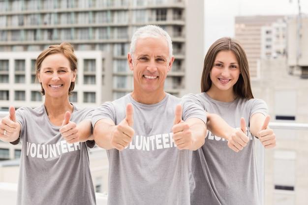 Улыбающиеся добровольцы делают большие пальцы